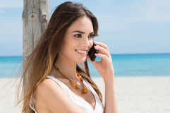 Young Woman Talking On Cellphone. Happy Young Woman At Beach Talking On Cellphone Stock Photography