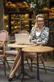 Young  woman talking on the cellphone while sitting with a laptop at an outdoor cafe. Royalty Free Stock Photography