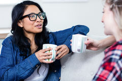 Young woman talking with female friend while drinking coffee Royalty Free Stock Photography