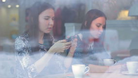 Young woman talking with friends and using smartphone in cafe stock video footage