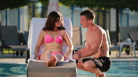 Young woman talking with her boyfriend near the swimming pool stock footage