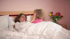 Young woman talking with her daughter girl in bedroom bed stock video