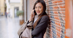 Young woman talking on her mobile in town Royalty Free Stock Photo