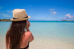 Young woman talking on her phone at tropical beach Stock Photos