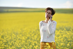 Young woman talking on her smart phone in the middle of a canola Royalty Free Stock Photography