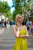 Young woman talking on her smart phone while standing in city street with people walking Royalty Free Stock Photo