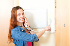 Young woman talking on the house videophone indoor. Young woman talking on the house videophone stock photo