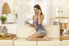 Young woman talking on mobile at home Royalty Free Stock Images