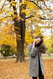 Young woman talking on mobile phone in autumn park Stock Image