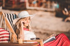 Young woman talking on a mobile phone on the beach royalty free stock image