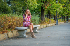 Young woman talking mobile phone in city park Royalty Free Stock Photography