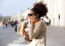 Young woman talking on mobile phone and eating outdoors Stock Photography