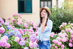 Young woman is talking on mobile phone. Happy girl with smile in garden with bushes of hydrangea. Pink, blue flowers are blooming in town street by house royalty free stock images