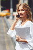 Young woman talking on mobile phone and holding paper Royalty Free Stock Photo