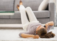 Young woman talking mobile phone while laying on floor Royalty Free Stock Images