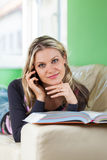 Young Woman Talking on a Mobile Phone While Lying at Home on the Royalty Free Stock Images