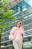 Young woman talking on mobile phone outside city building Royalty Free Stock Images