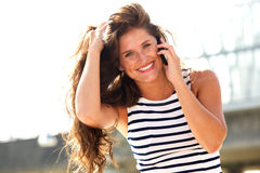 Young woman talking on mobile phone outside laughing Royalty Free Stock Photography