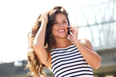 Young woman talking on mobile phone outside smiling Royalty Free Stock Images