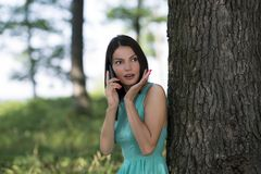 Young woman talking on mobile phone in park Stock Images