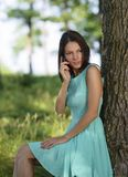 Young woman talking on mobile phone in park Royalty Free Stock Images