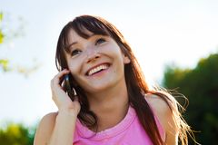 Young woman talking on mobile phone and smiling outdoors Royalty Free Stock Photography