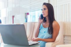 Young woman talking on mobile phone and smiling, sitting in front of the laptop in white hotel lobby stock photo