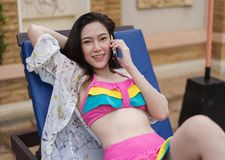 Young woman talking on mobile phone in the swimming pool. Young beautiful woman talking on mobile phone in the swimming pool royalty free stock photo
