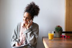 Young woman talking on mobile phone and taking notes Royalty Free Stock Image