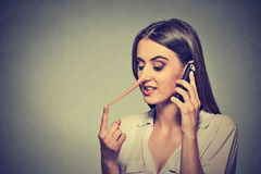 Young woman talking on mobile phone telling lies has a long nose. Portrait young woman talking on mobile phone telling lies has a long nose isolated on gray wall Stock Photos