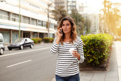 Young woman talking on mobile phone while walking Royalty Free Stock Photography