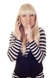 Young woman talking by mobile saying shh Stock Photos