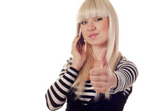 Young woman talking by mobile showing ok sign Royalty Free Stock Image