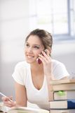 Young woman talking on mobile smiling. Attractive young woman talking on mobile phone, laying on floor, smiling Royalty Free Stock Photo