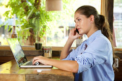 Young woman talking on mobile while working on laptop computer Royalty Free Stock Photos