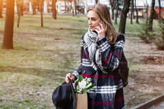 Young woman talking with parents on the phone walking on a sunny day in the park. Beautiful girl in a coat, hat and. Young woman talking with parents on the royalty free stock photography