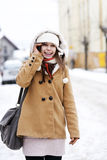 Young woman talking on the phone. Winter collection: portrait of beautiful woman in wintertime Stock Images