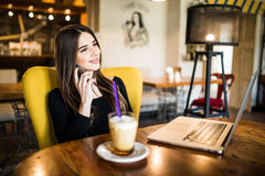 Young woman talking on the phone in coffee shop. Young beauty woman talking on the phone in coffee shop Stock Images