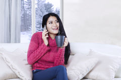 Young woman talking by phone on the couch Royalty Free Stock Photography