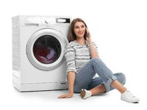 Young woman talking on phone while doing laundry. Against white background stock image