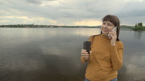 Young woman talking on the phone and drink coffee at the pond. stock video