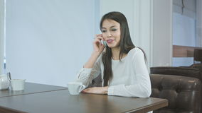 Young woman talking on the phone and drinking coffee or tea stock footage
