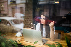 Young woman talking on the phone in front of laptop in coffee shop. Young woman talking on the phone in coffee shop Stock Photography