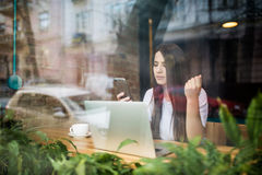 Young woman talking on the phone in front of laptop in coffee shop. Young woman talking on the phone in coffee shop Stock Photos