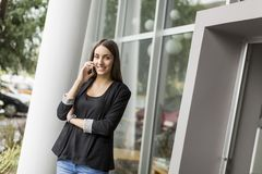 Young woman talking on the phone in front of office Stock Image
