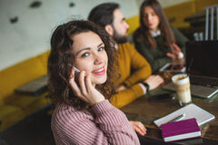 Young woman talking phone with happy friends in cafe Royalty Free Stock Photography