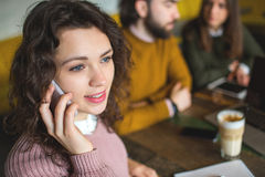 Young woman talking phone with happy friends in cafe Royalty Free Stock Photo