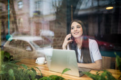 Young woman talking on the phone with laptop in coffee shop. Young woman talking on the phone in coffee shop Royalty Free Stock Photo