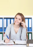 Young woman talking at phone and looking at camera Royalty Free Stock Image