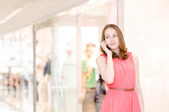 Young woman talking on the phone at the mall Royalty Free Stock Photo
